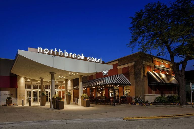 At night, the Northbrook Court sign is brightly shining on the building's main entrance with potted plants as decor.